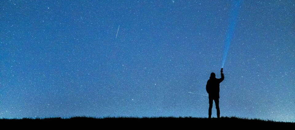 Figure of a man, standing against the backdrop of stars, shining a torch into the sky.