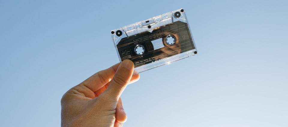 Someone holding up a casset tape, with the sky as a background.