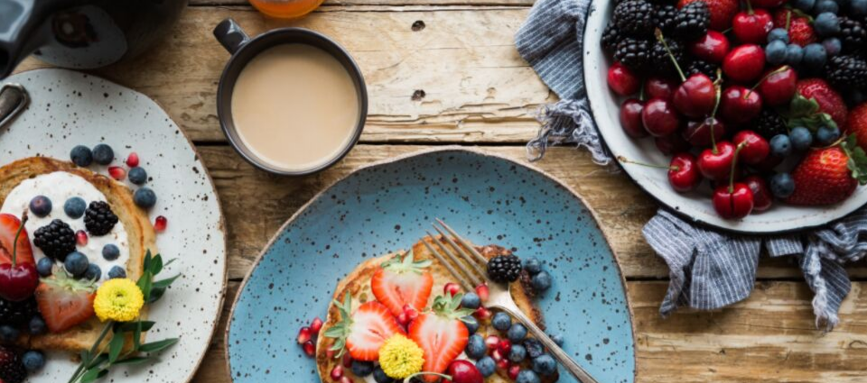 A breakfast scene featuring french toast, berries and weak coffee.