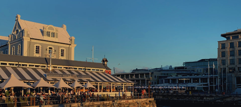 V&A Waterfront scene in Cape Town. Buildings, blue skies and people - smiling, eating and celebrating summer time.